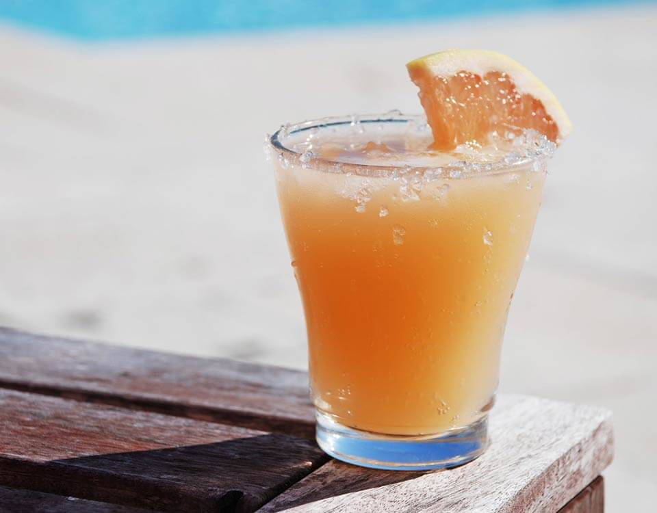 Sparkling grapefruit cocktail served in glass with grapefruit wedge outside by the pool
