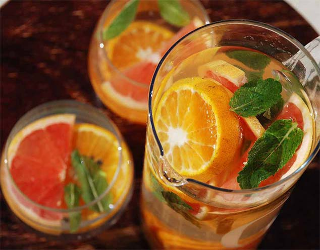 Grapefruit, Tangerine and Mint Infused Water in pitcher with two classes beside it with fruit slices in it