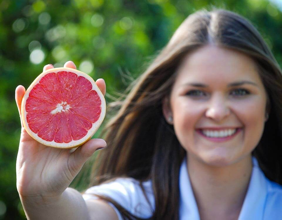 Young woman holding half of a SweeterSorts Florida Red Grapefruit