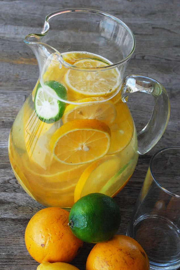 Citrus infused water in a clear pitcher with fruits around it.