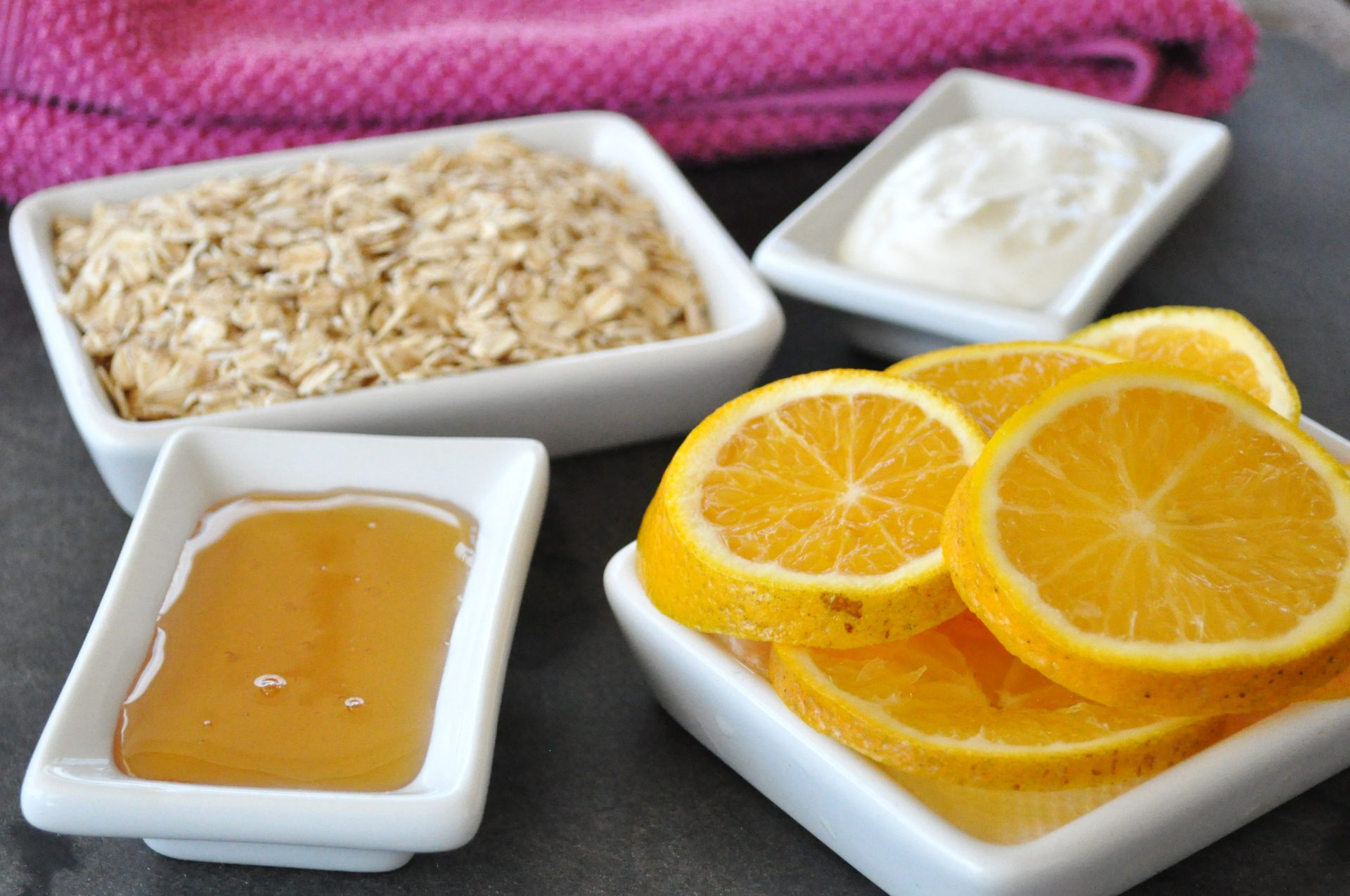 Moisturizing orange face mask ingredients laid out in white bowls on table