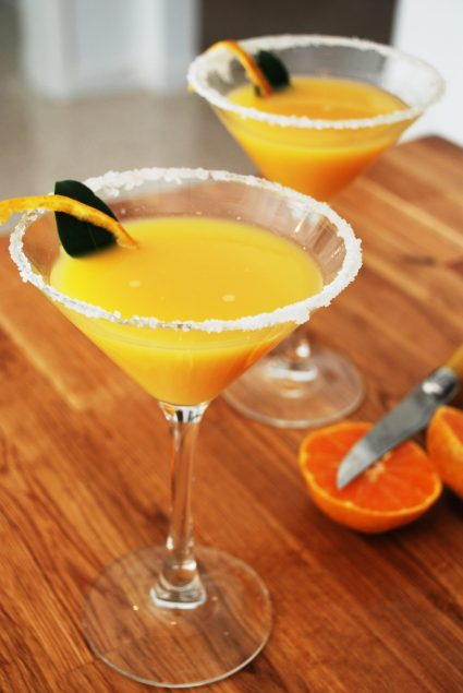 Homemade tangerine cocktail in martini glass with sugar rim on countertop