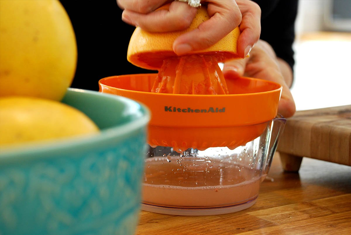 Someone juicing Fresh fruit (oranges) from SweeterSorts with KitchenAid juicer to make freshly squeezed juice