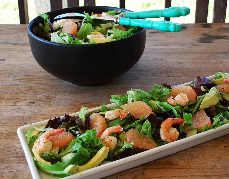 Shrimp Salad with Avocado & Grapefruit sitting on a wooden table