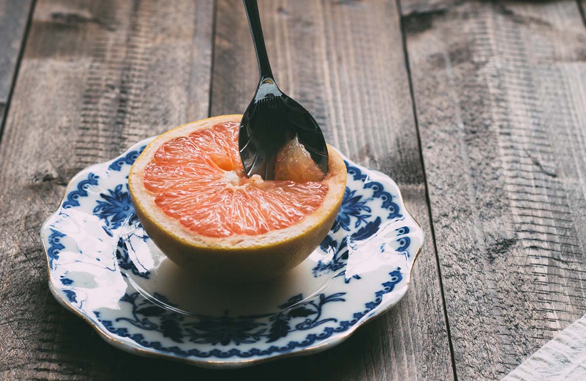 Sweetersorts grapefruit on blue plate on a wooden table with grapefruit spoon inside