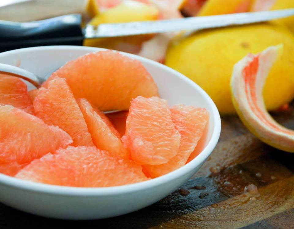 SweeterSorts segmented Florida grapefruit in white bowl with peel and knife in background