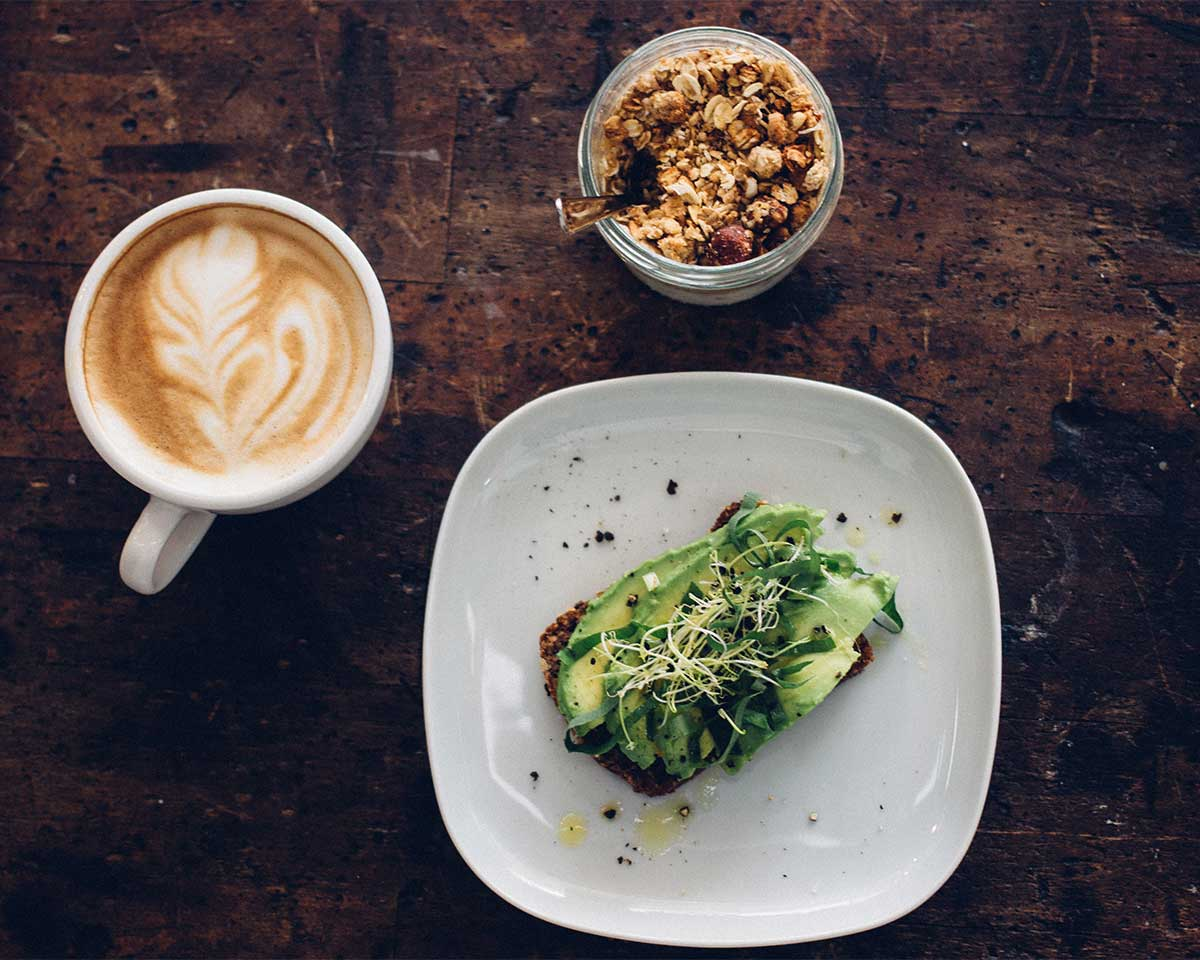 an appetizing shot of a plant based meal - avocado toast with sprouts and cracked pepper, a latte, and a granola parfait